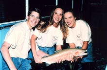 Three students pose with a steelhead trout at their fish hatchery. The studentsraised nearly over a half a million dollars to construct a fish hatchery.