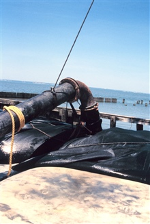 A dredge pipe filling a geotube.
