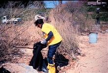 Margaret McCalla of NOAA cleans trash off the beach at Ft. McHenry, MD.