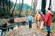 Dale Reiner and his brother are on the left. The Reiners and a NorthwestChinook Recovery board member, Rusty Wailes, examine the restored area.