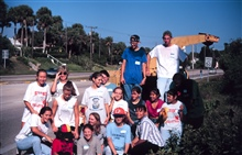 A local school group poses after the removal effort. Volunteers cut BrazilianPepper bushes from native mangrove habitat and then the County Roadworksuses a chipper to chip the bushes and dispose of the brush.