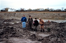 Local children stand in the low marsh area adjacent to the pre-restoredditch of a headwater stream.