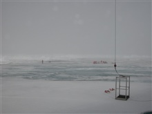Scientists work on the ice in foggy weather. The manlift in the foreground, raised and lowered by one of Healy's cranes, is their transportto and from the Healy.