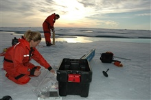 Rolf Gradinger works on an ice core while Mette Nielson takes measurementson a core already brought to the surface.