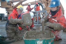 Katrin Iken (left) and Bodil Bluhm move deep-sea mud from the trawlnet to a bucket. The benthic scientists will sieve the mud to findcreatures within it for additional research.
