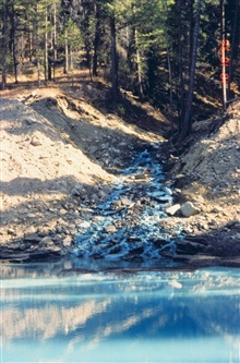 The distinct blue in this image is caused by copper contamination, BucktailCreek. Nothing lives in this environment. This image shows a collection basinused as part of the remediation. Water is shunted to a treatment plant.