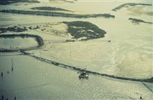 East Timbalier Island, booms are placed to contain oil. The island wasseriously impacted by Hurricane Andrew, after the oil blow out restorationplans included creating marshes near the breaks in the island to stabilize theisland.
