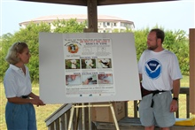 NOAA's John Iliff and a bird rehabilitator, Lee Fox, introduce a postercreated to educate volunteers about how to rescue injured birds.