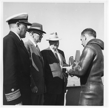 Rear Admiral H. Arnold Karo, Director of the Coast and Geodetic Survey, UnderSecretary of Commerce Allen, and Assistant Secretary of Commerce Mooreaboard C&GS; Ship GILBERT at Little Creek, Virginia.  Dr. Harris B. Stewart inwet suit is explaining op