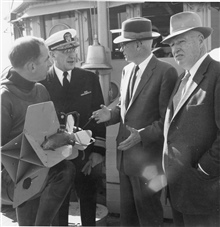 Dr. Harris B. Stewart in wet suit, Rear Admiral H. Arnold Karo, Under Secretaryof Commerce Allen, and Assistant Secretary of Commerce Moore on theC&GS; Ship GILBERT at Little Creek, Virginia.