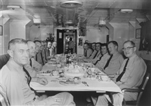 Wardroom of PATHFINDER, Captain Francis B. Quinn on right, CME Gilgan, Sam Baker, Dr. Gerald, then unidentified.  X. O. Ira Rubottomon left, Marvin Paulson, Harley Nygren, Dr. Peterson, unidentified to end of table.