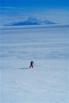 Photographer getting ready to set up for shot of Mount Erebus across sea ice.