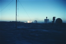 The first sunrays illuminating the generator exhaust at South Pole Station