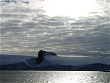 An angular mountain peak looking like the prow of a ship seemingly cuts throughan Antarctic Peninsula ice field.