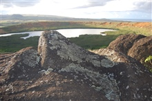 Lichen-covered rocks overlooking a small volcanic crater lake and marsh.